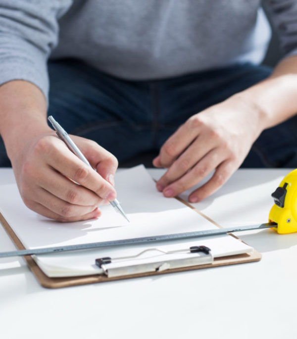 repair, building and home concept - close up of male hands writing in clipboard